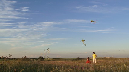 Father and daughter flying a kite in a summer field. Slow motion