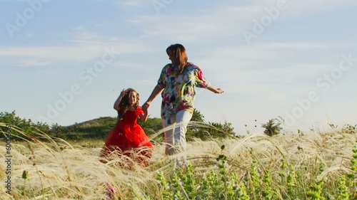 Mother and daughter running across summer field. Slow motion