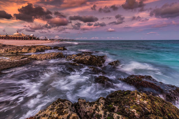 Purple sunset over a tropical rocky beach