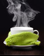 Coffee cup with smoke in green scarf on wooden table