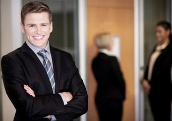 Businessman posing with smart associates behind