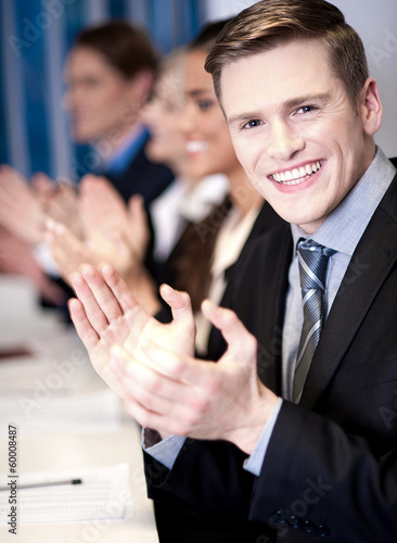 Business associates applauding, focus on guy