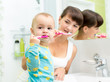 kid and mother brushing teeth