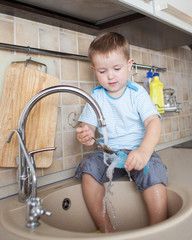 funny kid boy washing dish on kitchen
