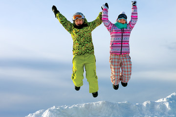 snowboarders friends in bright vivid clothes jumping