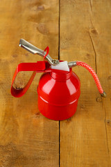 Red oil can, on wooden background