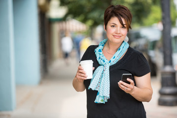 Woman With Coffee Cup Messaging On Smartphone