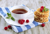 Cup of tea with cookies and raspberries on table close-up