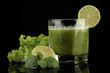 Glass of green vegetable juice and lime isolated on black