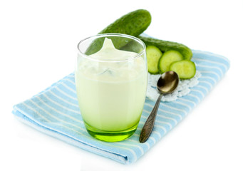 Cucumber yogurt in glass, on color napkin, isolated on white