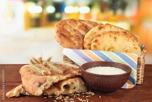Pita breads in basket with spikes and flour