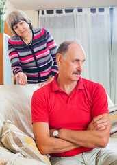 Tired mature man listening to angry wife