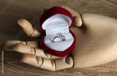 Box with ring in wooden hand isolated on white