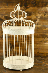 Beautiful decorative cage, on wooden background