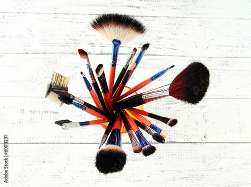 Makeup brushes in glass on wooden background