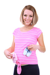 Young pregnant woman holding blue and pink baby shoes isolated