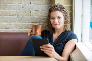 Woman With Coffee Mug And Digital Tablet In Cafe
