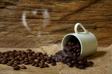 roasted coffee beans and heart smoke on wooden background,still