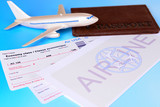 Airline tickets with passport on light blue background