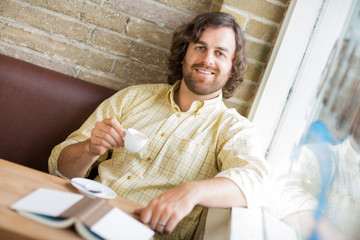 Man With Coffee Cup And Book In Cafe