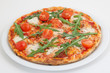 Pizza with tomato and arugula on white plate