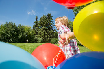 Boy With Balloons Running In Park