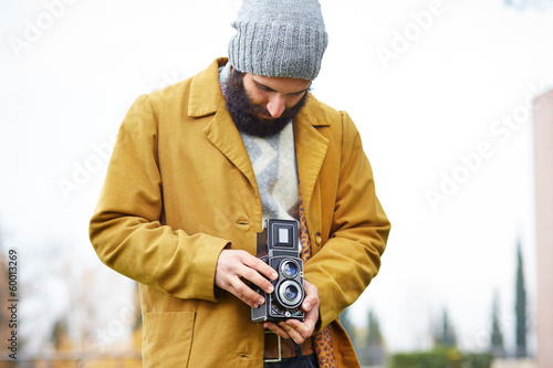 Young bearded hipster taking photo with TLR camera