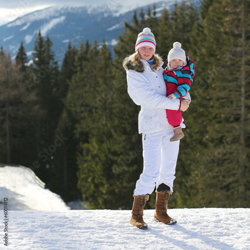 Happy young mother with toddler daughter in colorful snowsuit
