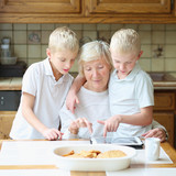 Teenager boys twin brothers teaching grandmother play on tablet