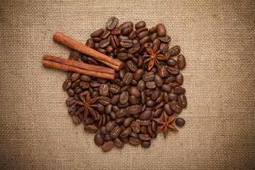 Coffee beans heap with spices on sack cloth background