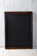 Vintage blank chalkboard on white wooden background