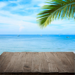 Empty wooden table with tropical sea and palm leaf on background