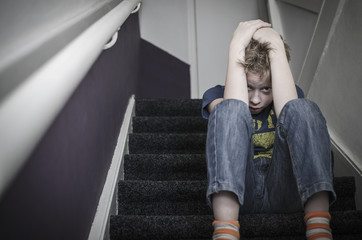 scared boy on stairs, child abuse