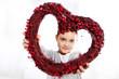 Kaukaska dziewczynka patrzy przez  czerwone walentynkowa serce