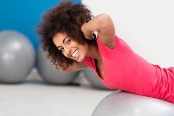 junge frau trainiert ihren rücken im fitnesscenter