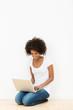 lächelnde schöne frau mit laptop auf dem fußboden