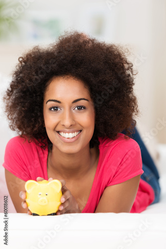 lächelnde junge frau mit sparschwein zu hause
