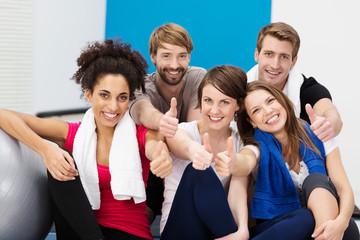 lachende gruppe zeigt daumen hoch im fitnessstudio
