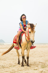 Asian girl riding horse on the beach