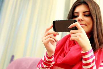 Young beautiful woman holding smartphone. Focus on smartphone.
