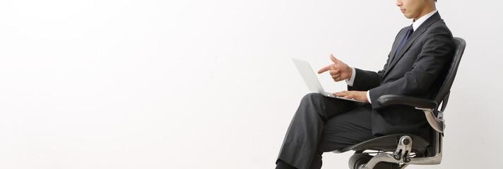 ノートパソコンを指差すビジネスマン