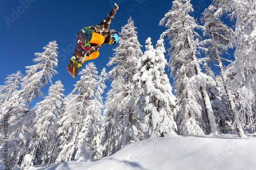 foresta ghiacciata con snowboarder in volo