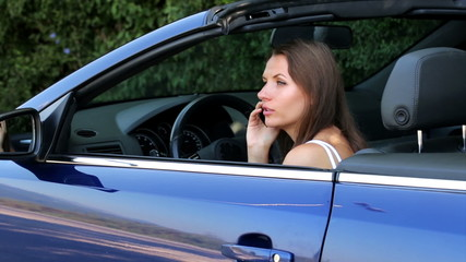 Cheerful girl sitting in a cabriolet car talking on the phone