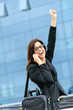 Successful businesswoman on the phone raising arm