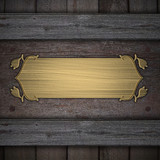 Wooden background with a gold plate with decoration