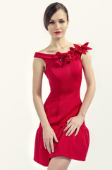 Brunette woman wearing an elegant red dress posing fashion