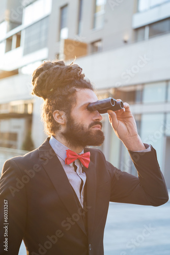Stylish elegant dreadlocks businessman binoculars