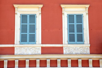 old french blue shutter windows in red house, Nice, France.