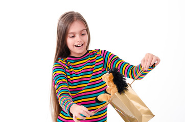 happy girl pulls out a toy horse package