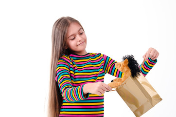 Girl looks at a gift bag with a toy horse